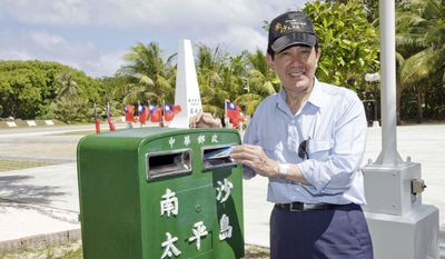 In this photo released by the Taiwan Presidential Office, Taiwan's President Ma Ying-jeou posts a letter in a mailbox during his visit to Taiping Island, also known as Itu Aba, in the Spratly archipelago, south of Taiwan, Thursday, Jan. 28, 2016. Outgoing President Ma, defying a rare criticism from key ally the United States, visited the island in the disputed South China Sea on Thursday to emphasize Taiwan's sovereignty claims in the increasingly tense region. (Taiwan's Presidential Office via AP)