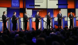 Republican presidential candidate John Kasich answers a question as Rand Paul, Chris Christie, Ben Carson, Ted Cruz, Marco Rubio and Jeb Bush listen during the Republican debate Thursday in Des Moines, Iowa. (Associated Press)