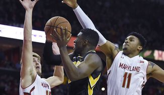 Maryland's Jake Layman, left, and Jared Nickens, right, defend against Iowa's Anthony Clemmons, center, in the first half of an NCAA college basketball game, Thursday, Jan. 28, 2016, in College Park, Md. (AP Photo/Gail Burton)
