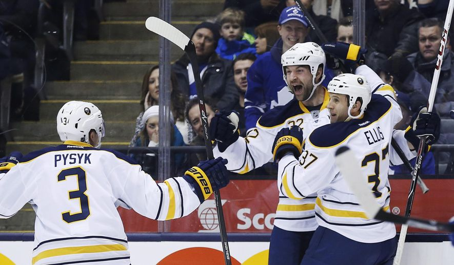 Buffalo Sabres' John Scott, center, celebrates his goal with teammates Mark Pysyk, left, and Matt Ellis against the Toronto Maple Leafs during the first period of an NHL hockey game Friday, Dec. 27, 2013, in Toronto. Scott took a shot at the NHL in a first-person story posted Thursday, Jan. 28, 2016, by The Players Tribune. He says someone from the league, who he did not identified, asked him if his children would be proud that he was playing in the All-Star game after being voted in by the fans. ( Mark Blinch/The Canadian Press via AP, File) MANDATORY CREDIT