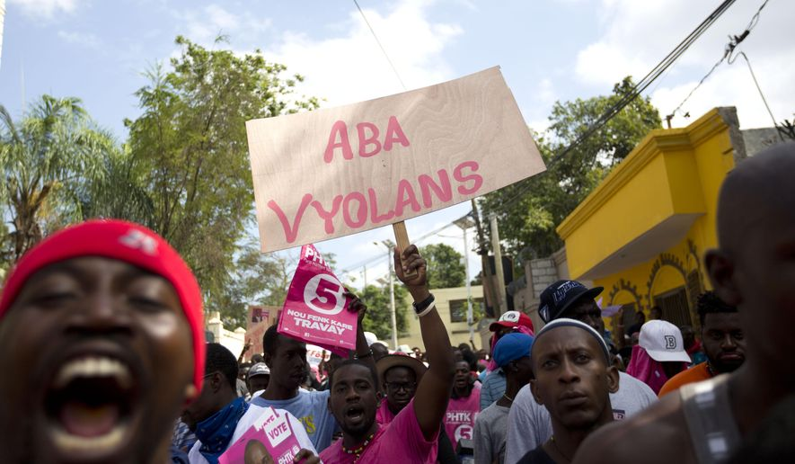 "A supporter of presidential candidate Jovenel Moise of the PHTK political party, holds up a sign that reads in Creole ""Down with violence"" during a march to demand elections in Port-au-Prince, Haiti, Thursday, Jan. 28, 2016. A presidential and legislative runoff was called off less than 48 hours before the Jan. 24 vote was set to begin amid a surge of violent protests and deep suspicion that a first round was rigged in favor of Moise, the ruling party's presidential candidate. (AP Photo/Dieu Nalio Chery)"