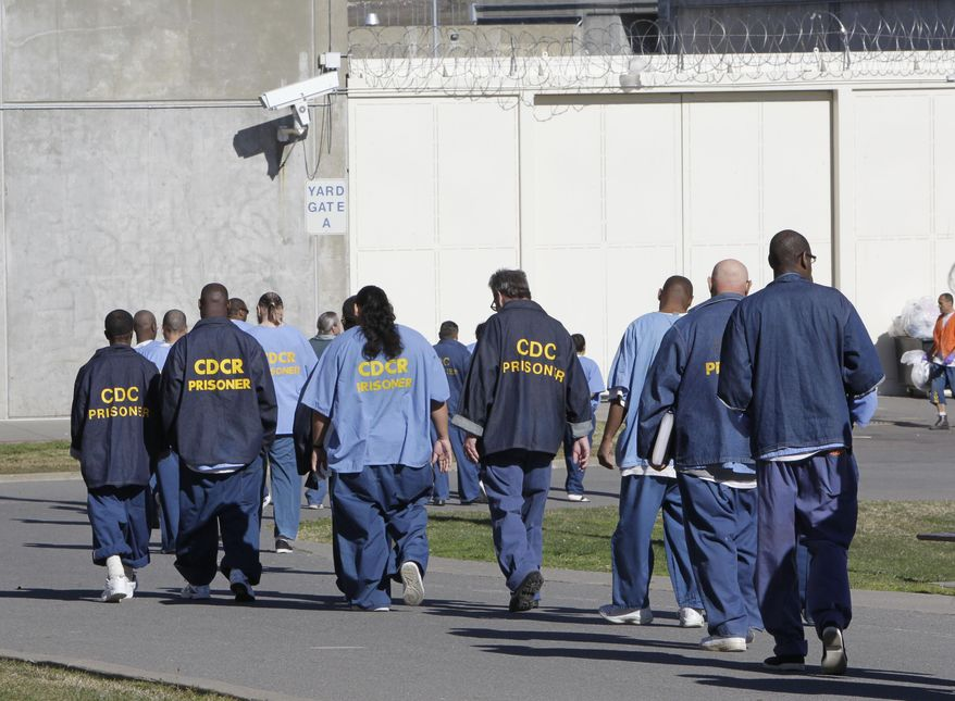 FILE - In this Feb. 26, 2013, file photo, inmates walk through the exercise yard at California State Prison Sacramento, near Folsom, Calif. Gov. Jerry Brown's latest attempt to reduce the state prison population is a ballot initiative unveiled Wednesday, Jan. 27, 2016, that aims to free certain felons earlier and have fewer juveniles tried as adults. (AP Photo/Rich Pedroncelli, File)
