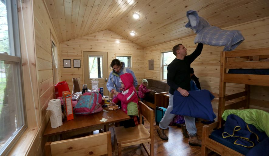 """ADVANCE FOR USE MONDAY, FEB. 1 - In this photo taken, Nov. 16, 2015, the Thompson family, of Tacoma, Wash., mom Julianne, dad David and kids Simon, 8; Cecilia, 6; Emilia, 4; and Marilyn, 2, unpack in their cabin at Dash Point State Park in Federal Way, Wash. """"We just wanted to find a place close by and get away from the daily grind,"""" said Julianne Thompson. (Ellen M. Banner/The Seattle Times via AP) SEATTLE OUT; USA TODAY OUT; MAGS OUT; TELEVISION OUT; NO SALES; MANDATORY CREDIT TO BOTH THE SEATTLE TIMES AND THE PHOTOGRAPHER"""