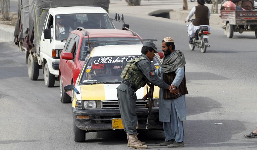 An Afghan policeman searches a passenger at a checkpoint in Kandahar, Afghanistan, Tuesday, Jan. 26, 2016. An Afghan official says that a policeman has turned his weapon on fellow police officers at a checkpoint in the country's south, killing 10 policemen. (AP Photo/Allauddin Khan)