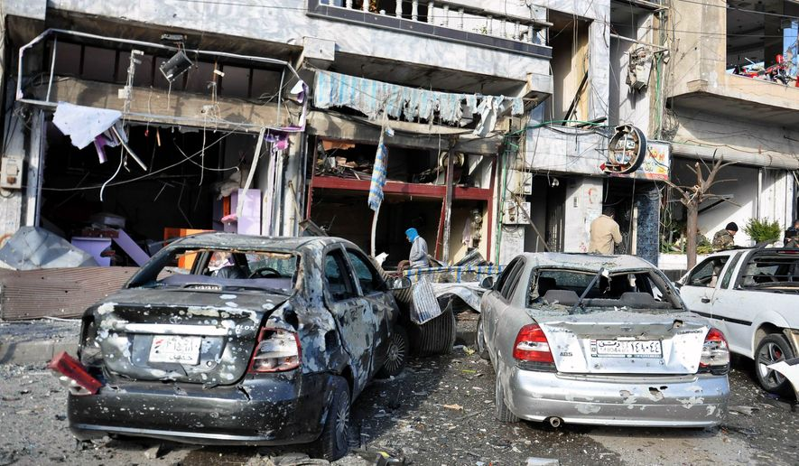 In this photo released by the Syrian official news agency SANA, Syrian citizens gather at the scene where twin bombs exploded at a government-run security checkpoint, at the neighborhood of Zahraa, in Homs province, Syria, Tuesday, Jan. 26, 2016. (SANA via AP) ** FILE **