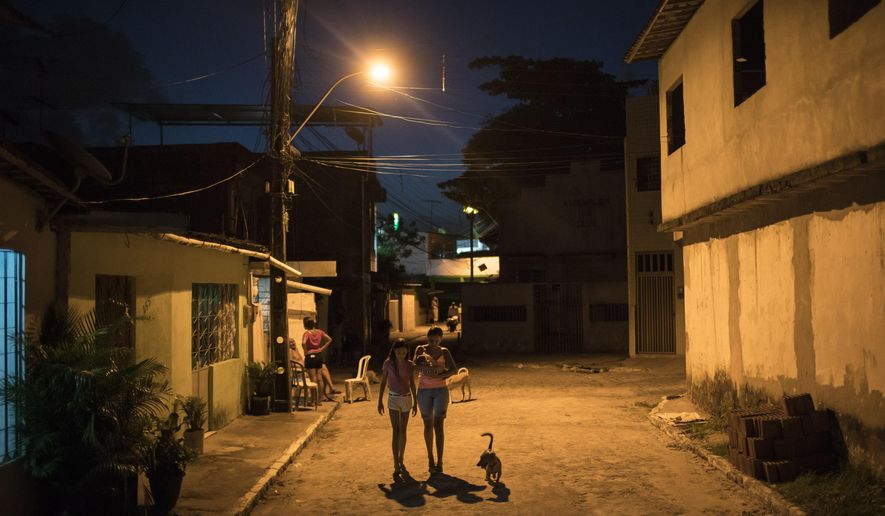 In this  Jan. 26, 2016 photo, Daniele Ferreira dos Santos, center, holds her son Juan Pedro as she walks with her older daughter Jennipher Karine near her house in Recife, Pernambuco state, Brazil. Around the fifth month of her pregnancy, Daniele Ferreira dos Santos fell ill with a high fever and angry red splotches on her skin. She soon recovered. But weeks later, when she went to the hospital for a prenatal exam, the news was horrific: The baby she was carrying likely had a severe brain injury. (AP Photo/Felipe Dana)