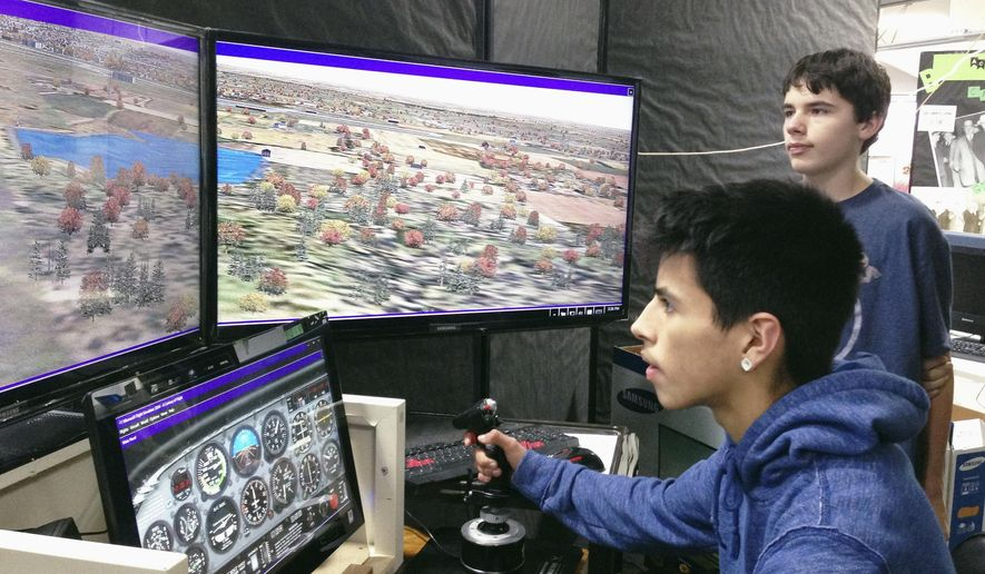 In this Jan. 7, 2016 photo, Jefferson High School sophomore Joseph Martins watches freshman Brian Angel fly a plane using a simulator at Jefferson's annual Pick My Pathway career-exploration event in Rockford, Ill. Freshman got the chance to learn more about the school's 22 academic pathways from dozens of experts: upperclassmen at Jefferson. (Corina Curry/Rockford Register Star via AP)  MANDATORY CREDIT