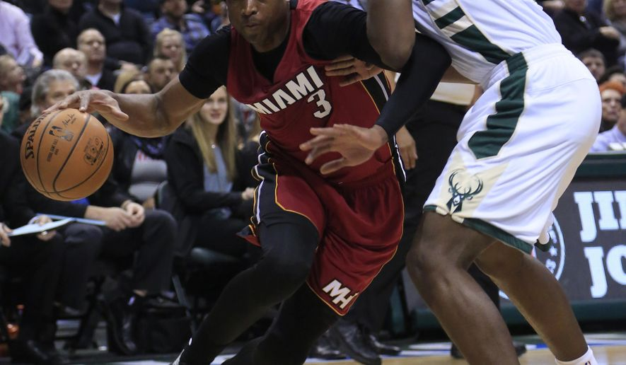 Miami Heat guard Dwyane Wade, left, drives to the basket against Milwaukee Bucks guard Khris Middleton, right, during the first half of an NBA basketball game Friday, Jan. 29, 2016, in Milwaukee. (AP Photo/Darren Hauck)