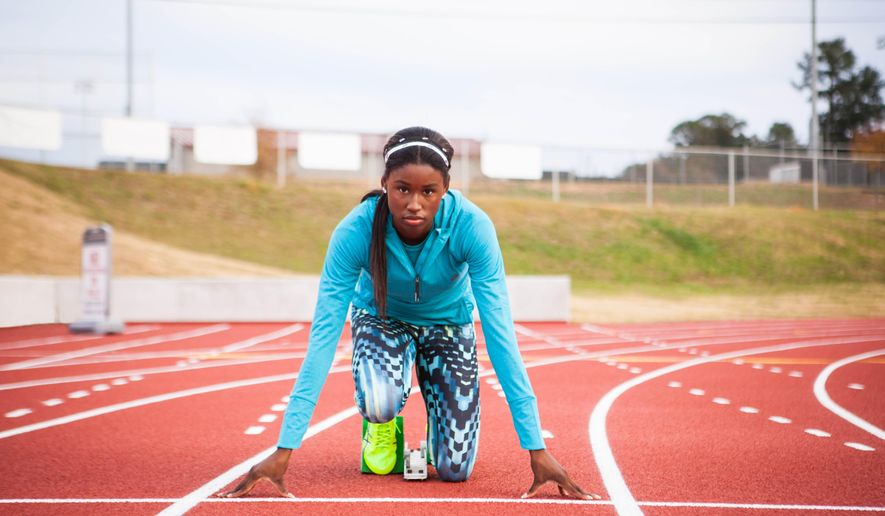 In this image taken in December 2015, and provided by ASICS America, American sprinter Candace Hill poses at Rockdale County High School Track in Conyers, Ga. Hill's favorite subject in high school is U.S. history. Certainly appropriate, since the 16-year-old from Atlanta is making quite a bit of it on the track. World history, for that matter, with her fast times. Later this year, maybe even some Olympic history, too, as the youngest sprinter ever to make the American squad. (ASICS America via AP)