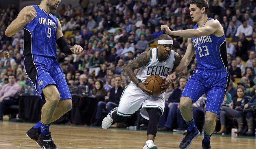 Boston Celtics guard Isaiah Thomas (4) drives between Orlando Magic center Nikola Vucevic (9) and guard Mario Hezonja (23) during the first quarter of an NBA basketball game Friday, Jan. 29, 2016, in Boston. (AP Photo/Elise Amendola)