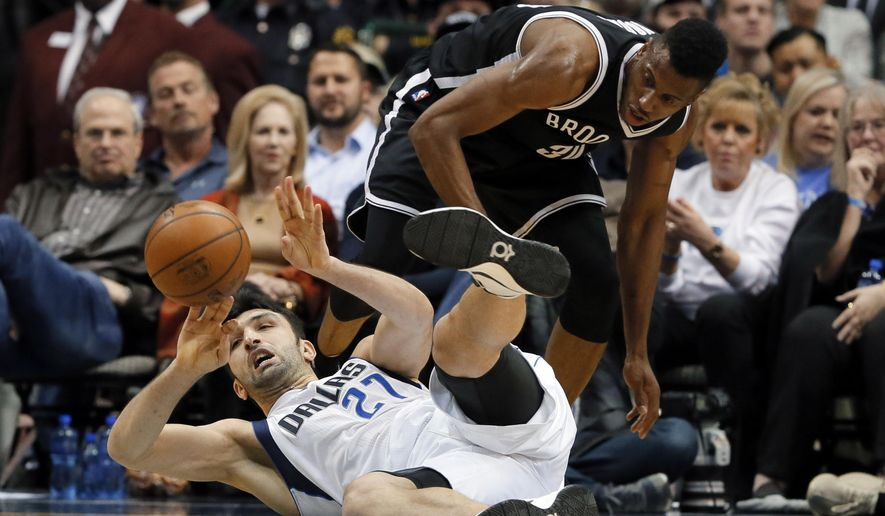 Dallas Mavericks center Zaza Pachulia (27), of Georgia, passes the ball after recovering it on the floor in front of Brooklyn Nets' Thaddeus Young (30) in the first half of an NBA basketball game, Friday, Jan. 29, 2016, in Dallas. (AP Photo/Tony Gutierrez)