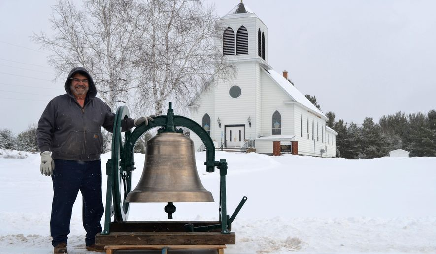 In this photo taken on Tuesday, Jan. 26, 2016, Guy Forstrom displays the restored St. Mary Catholic Church bell outside the old church building, now the Christ Temple Church, in Quinnesec, Mich. The bell, which had been in storage at the Menominee Range Historical Museum for 20 years, was recently returned to Breitung Township, where it will be displayed outside the township hall. (Nikki Younk/The Daily News via AP) MANDATORY CREDIT