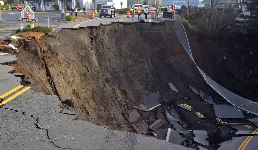 This Jan. 28, 2016, photo provided by the Oregon Department of Transportation shows a massive sinkhole that has opened up on a road near Highway 101 in the Curry County town of Harbor, Ore. Signs have been placed along the highway directing traffic to a detour.(Oregon Department of Transportation via AP)
