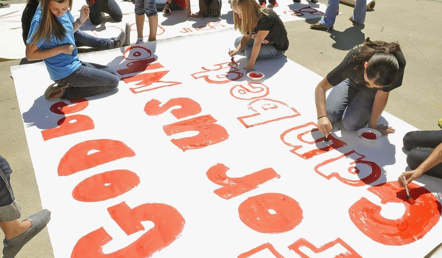 FILE - In this Sept. 19, 2012 file photo, Kountze High School cheerleaders and other children work on a large banner in Kountze, Texas. The Texas Supreme Court has ruled in favor of Kountze High School cheerleaders who argued their free speech was trampled by their school district when it ordered them not to display banners emblazoned with Bible verses at football games. (AP Photo/The Beaumont Enterprise, Dave Ryan, File)