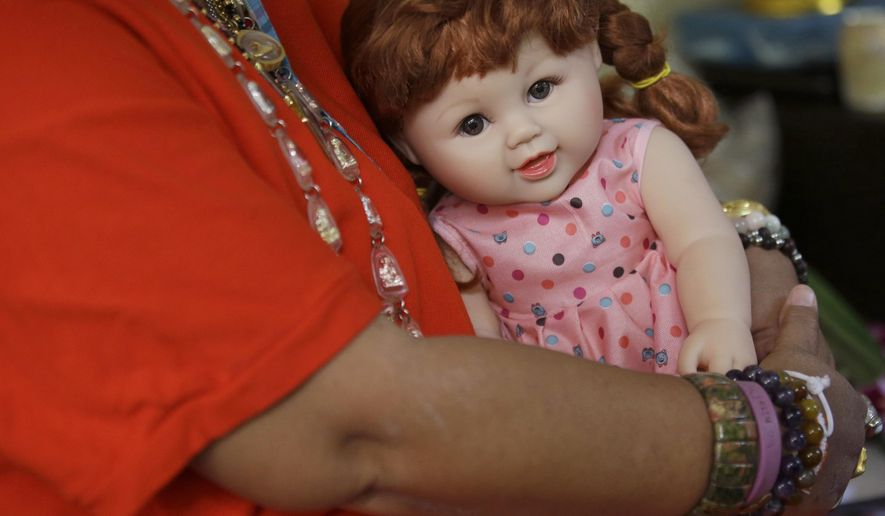 "In this Thursday, Jan. 28, 2016 photo, a Thai woman holds a ""child angel"" doll in Bangkok. Thailand. The dolls, which are said to bring good luck to their owners, became a media sensation this week after a leaked memo from a Thai budget airline gave pointers on how they could be treated like passengers if they have a paid-for seat. Thai people are superstitious, and the doll phenomenon has been analyzed as a modern version of a traditional totem containing real body parts, but as a fad it seems have more in common with Furby dolls. (AP Photo/Sakchai Lalit)"