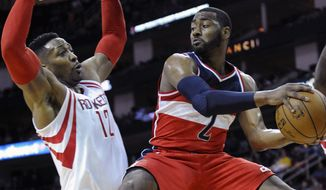 Washington Wizards' John Wall (2) looks to pass around Houston Rockets' Dwight Howard (12) in the first half of an NBA basketball game Saturday, Jan. 30, 2016, in Houston. (AP Photo/Pat Sullivan)