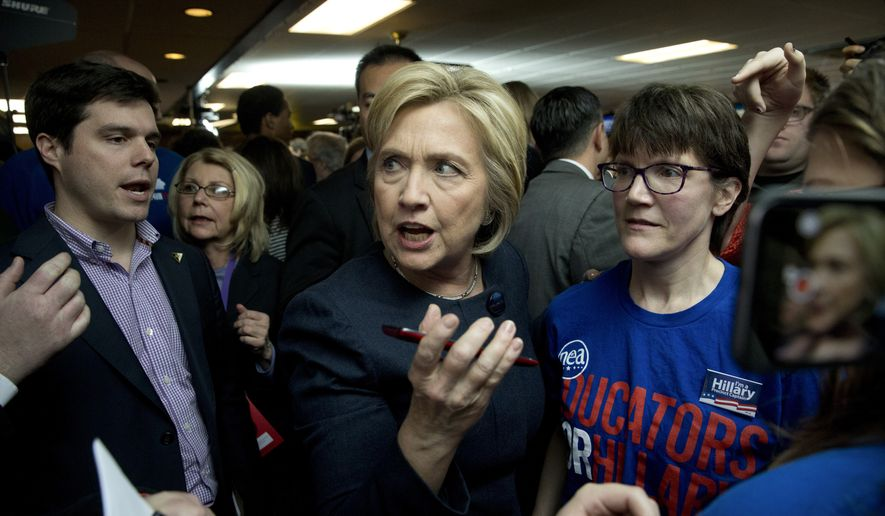 Democratic presidential candidate Hillary Clinton, center, hands a smartphone to her aide for photos with supporters at a campaign event at Adel Family Fun Center Wednesday, Jan. 27, 2016, in Adel, Iowa. (AP Photo/Jae C. Hong)