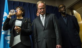 Flint Mayor Karen Weaver drinks from a bottle of water beside Michigan Department of Environmental Quality Director Keith Creagh as Gov. Rick Snyder fields questions from reporters about the Flint water crisis. (Jake May /The Flint Journal-MLive.com via AP) LOCAL TELEVISION OUT; LOCAL INTERNET OUT; MANDATORY CREDIT