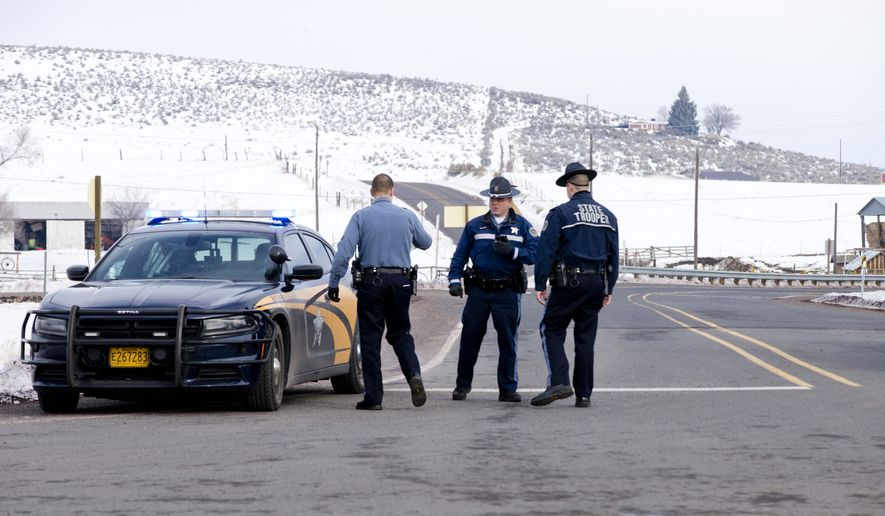 Oregon State Police man a roadblock at the intersection of highways 395 and 20 outside of Burns, Ore., Wednesday morning, Jan. 27, 2016. Authorities were restricting access on Wednesday to the Malheur National Wildlife Refuge headquarters being occupied by an armed group after one of the occupiers was killed during a traffic stop and eight more, including the group's leader Ammon Bundy, were arrested. (Dave Killen/The Oregonian via AP)