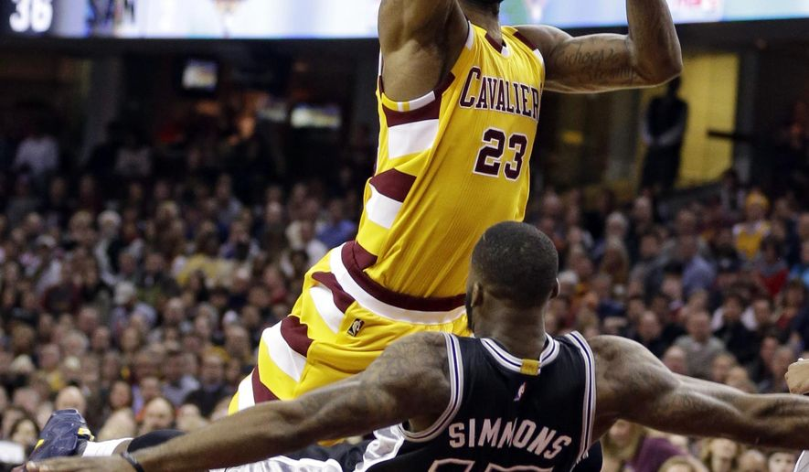 Cleveland Cavaliers' LeBron James (23) is fouled by San Antonio Spurs' Jonathon Simmons (17) in the first half of an NBA basketball game Saturday, Jan. 30, 2016, in Cleveland. (AP Photo/Tony Dejak)