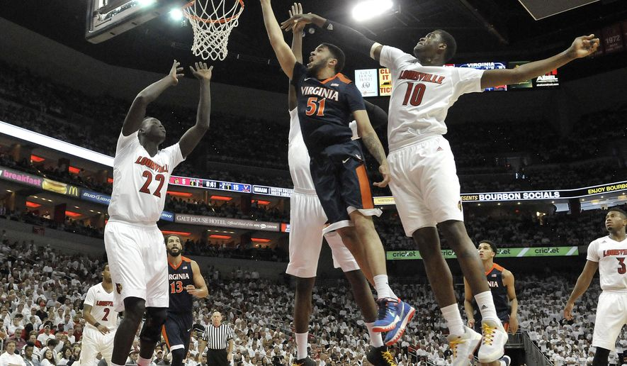 Virginia's Darius Thompson (51) goes in for a layup through the defense of Louisville's Deng Adel (22) and Jaylen Johnson (10) during the first half of an NCAA basketball game, Saturday, Jan. 30, 2016, in Louisville, Ky. Virginia won 63-47. (AP Photo/Timothy D. Easley)