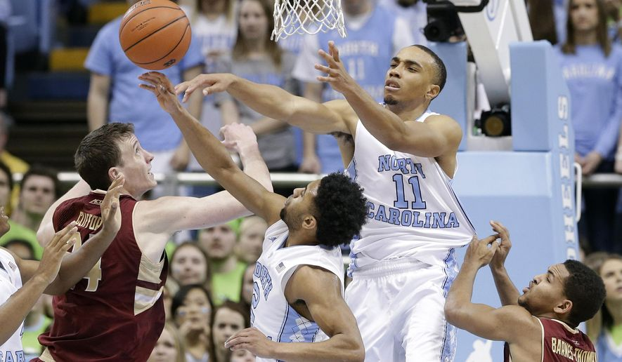 North Carolina's Brice Johnson (11) and Joel Berry II reach for a rebound with Boston College's Dennis Clifford, left, and Sammy Barnes-Thompkins (55) during the first half of an NCAA college basketball game in Chapel Hill, N.C., Saturday, Jan. 30, 2016. (AP Photo/Gerry Broome)