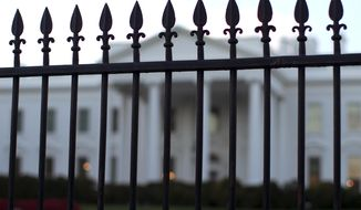 In this Sept. 23, 2014, file photo, the White House is seen through the North Lawn perimeter fence in Washington. (AP Photo/Carolyn Kaster, File)