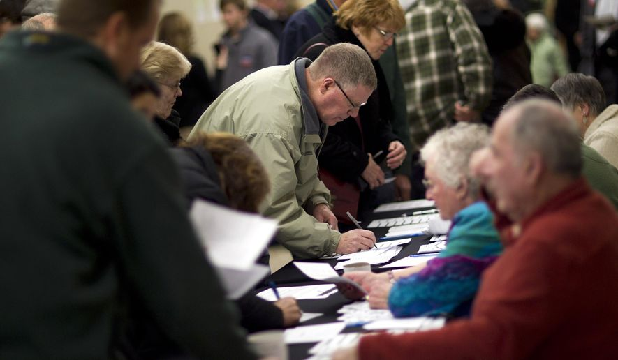 FILE - In this Jan. 3, 2012 file photo, voters sign in on caucus night at Point of Grace Church in Waukee, Iowa. More than 40 years ago, a scheduling quirk vaulted Iowa to the front of the presidential nominating process, and ever since most White House hopefuls have devoted enormous time and money to a state that otherwise would get little attention.  (AP Photo/Evan Vucci, File)