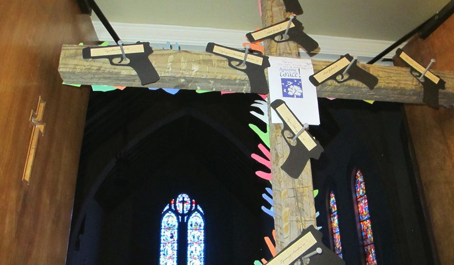 A cross with cutouts of handguns and the names of the nine victims of the Charleston church shootings stands at the door to the chapel at Washington Street United Methodist Church in Columbia, S.C., on Friday, Jan. 29, 2016. Parishioners attending a Stand-Up Sunday service at the chapel on Jan. 31 will pass under the cross. An estimated 1,300 congregations of all denominations in South Carolina are participating in the Stand-Up Sunday to draw attention to the national epidemic of gun violence and seek tighter gun laws while respecting people's rights to own guns. (AP Photo/Bruce Smith)