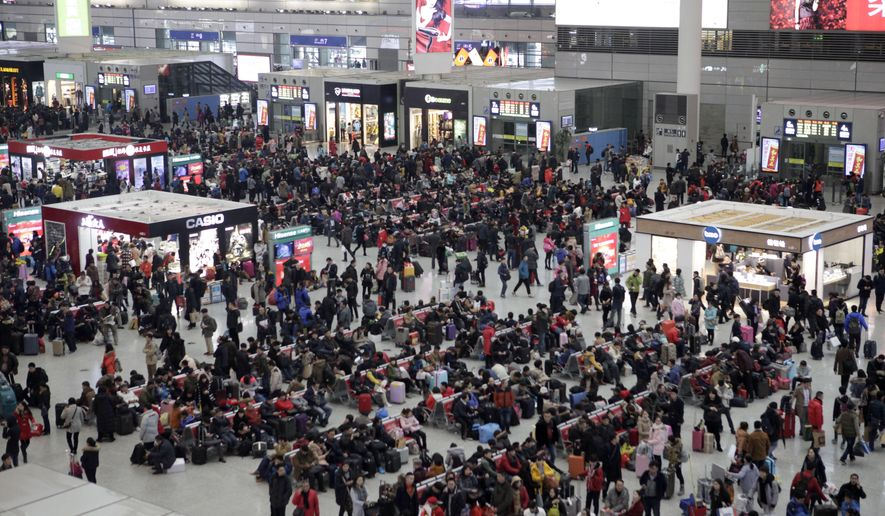 People sit in waiting areas at the Shanghai Hongqiao Railway Station in Shanghai, Friday, Jan. 29, 2016. Hundreds of thousands of passengers passed through Shanghai's railway stations on Friday in preparation for the upcoming Chinese New Year holiday, and according to state media, an estimated 2.91 billion journeys are expected to be made this year during the holiday period, traditionally a time for China's citizens to travel home and be with family and friends. (AP Photo)