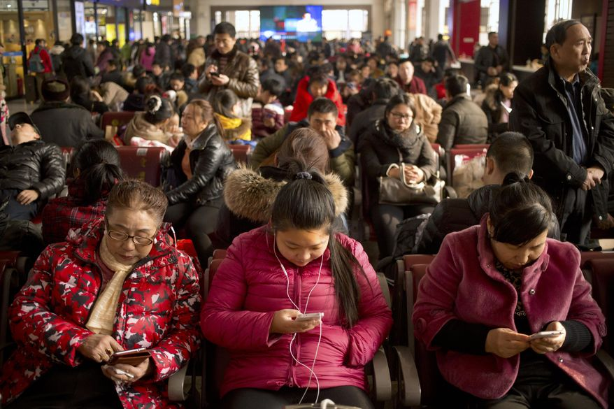 Passengers use their smartphones as they sit in a waiting room at the Beijing Railway Station in Beijing, Saturday, Jan. 30, 2016. China's peak travel season is kicking into high gear as hundreds of millions of people return home for Spring Festival celebrations or head for vacation destinations. According to the Ministry of transport, Chinese travelers are expected to make 2.9 billion trips during the 40-day period between Jan. 21 and March 3, with the majority of those trips falling in the weeks around the Feb. 8 Lunar New Year. (AP Photo/Mark Schiefelbein)