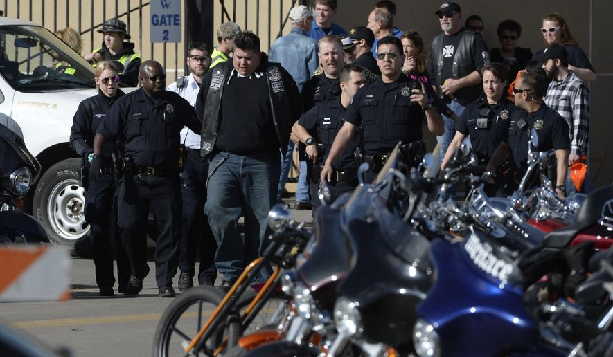 Denver Police escort a man in handcuffs away from the National Western Complex, Saturday, Jan. 30, 2016, in Denver. Denver police say multiple people were injured in a deadly stabbing and shooting at The Colorado Motorcycle Expo. (Andy Cross/The Denver Post via AP) MAGS OUT; TV OUT; INTERNET OUT; NO SALES; NEW YORK POST OUT; NEW YORK DAILY NEWS OUT; MANDATORY CREDIT