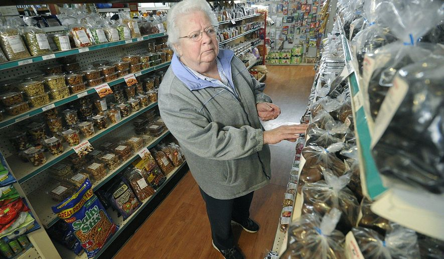 """In this Jan. 8, 2016, photo, Titusville resident Marilynn Moore looks for chocolate-covered raisins at Schrock's General Store in Rome Township, near Spartansburg, Pa. Schrock's has been the Spartansburg area's """"Amish Wal-Mart"""" for 26 years. (Greg Wohlford/Erie Times-News via AP)"""