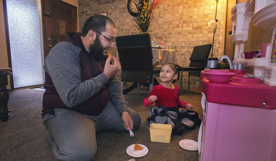"ADVANCE FOR THE WEEKEND OF JAN. 30-31 AND THEREAFTER - In a Jan. 18, 2016 photo, Imam Ahmad Saleh pretends to eat pizza ""prepared"" by his four-year-old daughter, Toka, at their apartment in University Place in Tacoma, Wa. Saleh said Toka is learning from the best. His wife, fellow Egyptian Sara Abdelwahab, is a wonderful cook. (Drew Perine/The News Tribune via AP)"