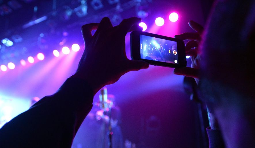 ADVANCE FOR USE SATURDAY, JAN. 30 - In this photo taken Dec. 30, 2015, Michael Lungren records video on his cell phone during a Yonder Mountain String Band concert at the Boulder Theater in Boulder, Colo. Z2 Entertainment, a virtual gatekeeper for national-level concerts in Boulder, operates the city's two main music venues, the Boulder and Fox theaters. And, in October, the company announced it had become the exclusive promoter of summer concerts at Chautauqua Auditorium. (Jeremy Papasso/Daily Camera via AP) NO SALES; MANDATORY CREDIT