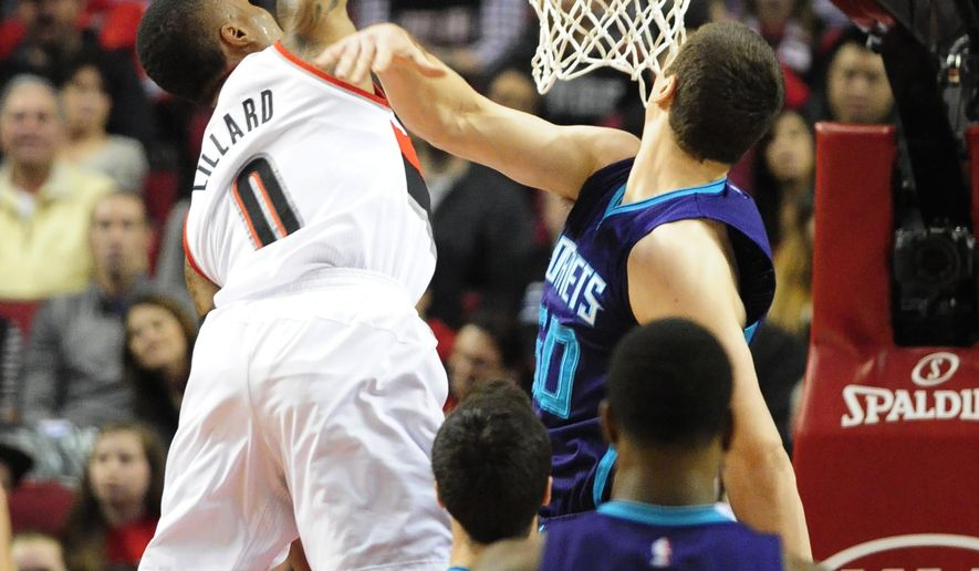 Portland Trail Blazers guard Damian Lillard (0) dunks against Charlotte Hornets forward Tyler Hansbrough (50) during the first half of an NBA basketball game in Portland, Ore., Friday, Jan. 29, 2016. (AP Photo/Steve Dykes)