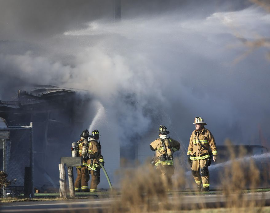 Firefighters work to extinguish a fire at Viking Wholesale after it had spread from the neighboring Bluegrass Stockyards on Saturday, Jan. 30, 2016, in Lexington, Ky. Lexington Fire Department spokesman Joe Best said Saturday the blaze was one of the largest he has seen in his 25 years with the department.(AP Photo/David Stephenson)