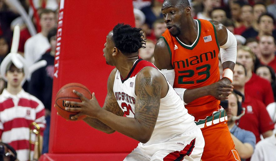North Carolina State's BeeJay Anya (21) battles under the basket  with Miami's Tonye Jekiri (23) under the basket during the first half of an NCAA college basketball game in Raleigh, N.C., Saturday, Jan. 30, 2016. (AP Photo/Karl B DeBlaker)