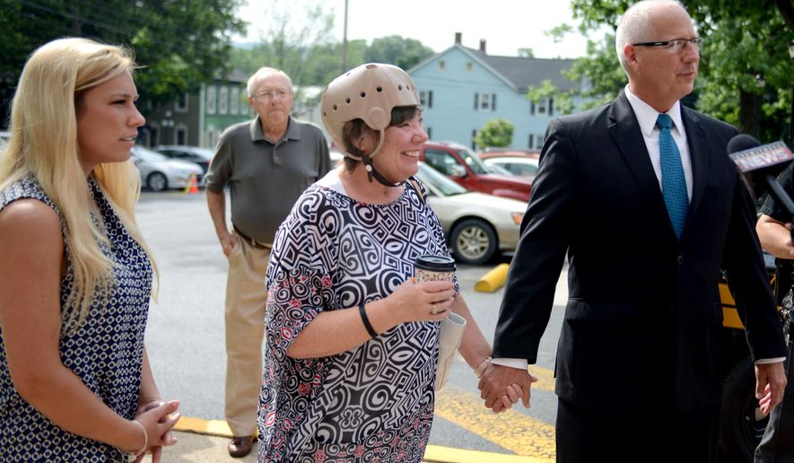 FILE - In this June 23, 2015, file photo, Sharon and Randy Budd, right, along with their daughter Kaylee, left, enter the Union County Courthouse in Lewisburg, Pa. Sharon Budd, a middle-school teacher who lives near Akron, Ohio, suffered head injuries when a rock dropped from an overpass crashed through the windshield of her family's car in Pennsylvania in July 2014. Thanks in part to efforts by Sharon Budd and her family, a change in Ohio Department of Transportation rules took effect Friday, Jan. 1, 2016, that requires new or rehabbed bridges over most busy roadways in Ohio to have fencing to deter vandals. (Amanda August/The Daily Item via AP, File)