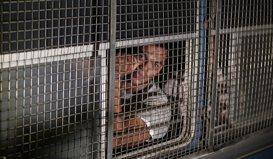 Yoshitha Rajapaksa, son of former Sri Lankan president Mahinda Rajapaksa shows hand cuffs to the media as he is  taken away in a prison bus from a magistrate court in Kaduwela, outskirts of Colombo, Sri Lanka, Saturday, Jan. 30, 2016. Sri Lanka's police on Saturday arrested the son of the country's former strongman leader over an alleged financial offense, an official said. (AP Photo/Eranga Jayawardena)