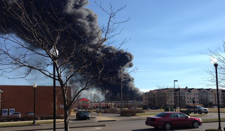 Smoke rises from a large fire in Lexington, Ky., Saturday, Jan. 30, 2016. Authorities say the large fire at the Blue Grass Stockyards complex has spread to other businesses. (AP Photo/Adam Beam)