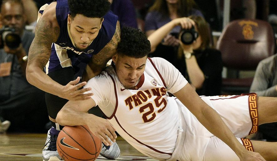 Washington guard David Crisp, left, and Southern California forward Bennie Boatwright, right, vie for a loose ball during the first half of an NCAA college basketball game in Los Angeles, Saturday, Jan. 30, 2016. (AP Photo/Kelvin Kuo)
