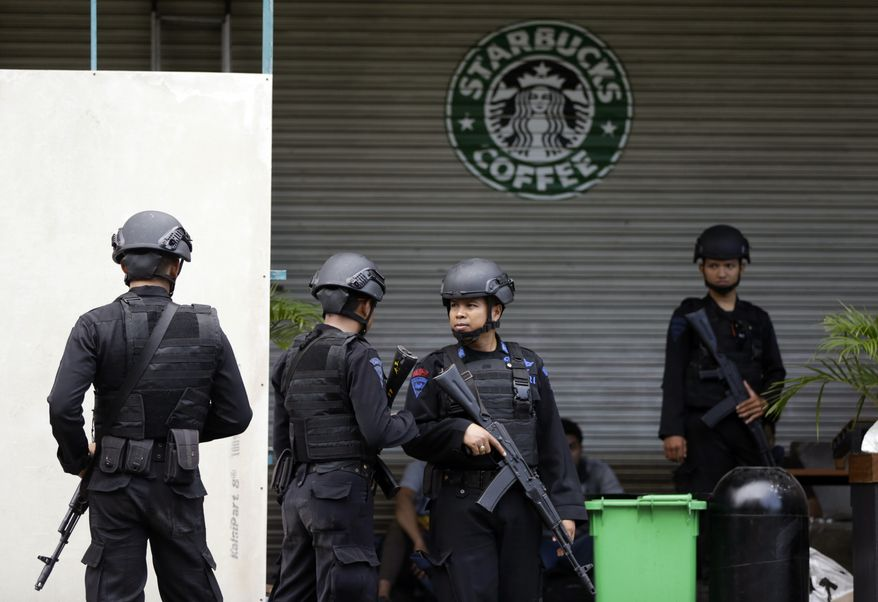 Indonesian police officers guard a Starbucks cafe in Jakarta, Indonesia, on Jan. 16, two days after it was a target of a suicide bombing attack funded by the Islamic State. (Associated Press) **FILE**