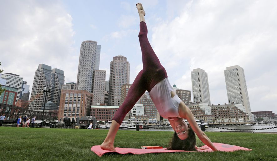 In this Aug. 25, 2015, photo, Sara DiVello sits in a modified lotus pose in the Financial District of Boston. DiVello, who stayed for years at a financial services company in Boston despite the fact she had an abusive boss, is now a yoga teacher. (AP Photo/Charles Krupa)