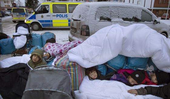 Migrant children Nor, Saleh and Hajaj Fatema from Syria sleep outside the Swedish Migration Board, in Marsta, Sweden. Interior Minister Anders Ygeman says Sweden could deport between 60,000 and 80,000 asylum-seekers in coming years. (Jessica Gow/TT News Agency via AP, File)