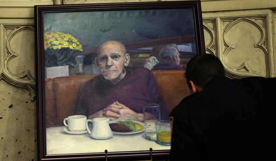 "A police officer gets a closer look at a painting of Abe Vigoda during his funeral service in New York, Sunday, Jan. 31, 2016. The actor who played Phil Fish on the 1970s TV series ""Barney Miller"" and Sal Tessio in the classic movie ""The Godfather"" was mourned at a funeral Sunday in New York. Vigoda died Tuesday in his sleep at age 94. (AP Photo/Seth Wenig)"