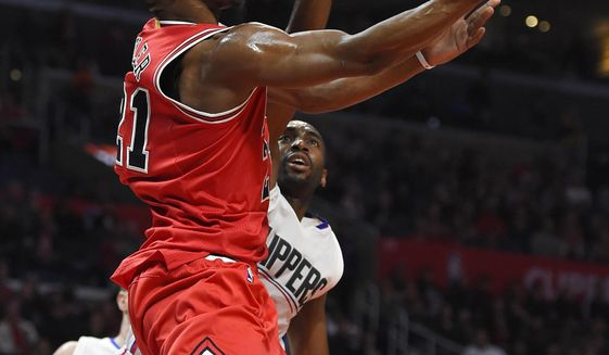 Chicago Bulls guard Jimmy Butler, left, shoots as Los Angeles Clippers forward Luc Richard Mbah a Moute, of Cameroon, defends during the first half of an NBA basketball game, Sunday, Jan. 31, 2016, in Los Angeles. (AP Photo/Mark J. Terrill)