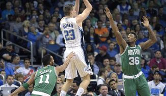 Orlando Magic guard Mario Hezonja (23) goes up for a shot between Boston Celtics guard Evan Turner (11) and guard Marcus Smart (36) during the first half of an NBA basketball game in Orlando, Fla., Sunday, Jan. 31, 2016. (AP Photo/Phelan M. Ebenhack)