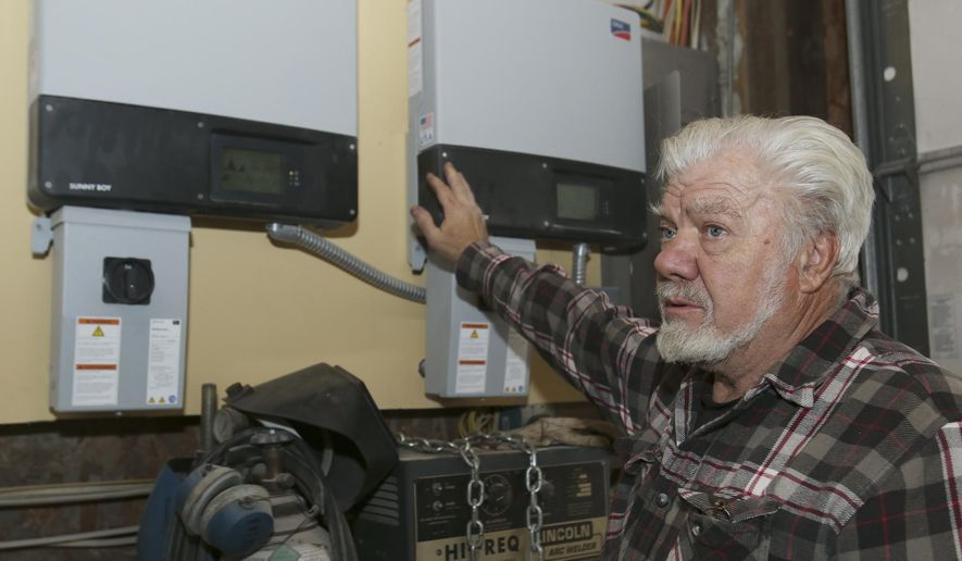 ADVANCE FOR USE SUNDAY, JAN. 31 - In this photo taken Jan. 20, 2016, Tim Smith talks about the controls for solar panels he installed on his roof in Hastings, Neb. Smith is taking advantage of LB 436, which allows customers to sell unused power back to electrical suppliers at wholesale cost. (Laura Beahm/The Hastings Tribune via AP) MANDATORY CREDIT