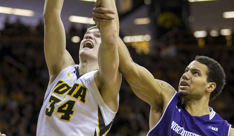 Iowa center Adam Woodbury is grabbed by Northwestern forward Joey van Zegeren as he rebounds the ball during the first half of an NCAA college basketball game, Sunday, Jan. 31, 2016, in Iowa City, Iowa. (AP Photo/Justin Hayworth)